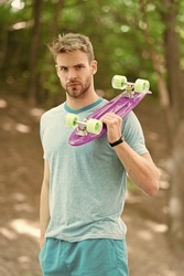 Penny board is his travel companion. Handsome guy hold penny board outdoors. Athletic skater with pink board. Speed and balance. Recreational activity. Action sport. Riding in style on board