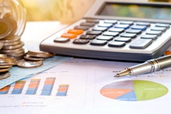 Pens and coins placed on financial reports or stock market graph analysis.