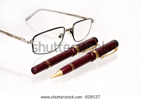 Pens and glasses on a table.