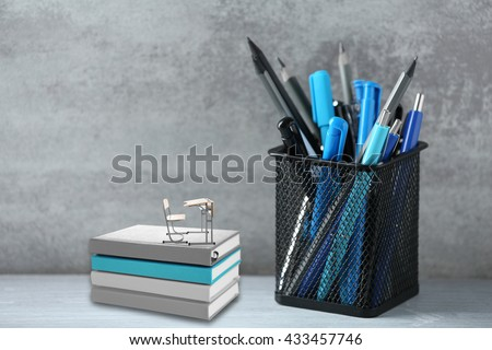 Pens and pencils in metal holder, notebooks with small wooden desk and chair on wall background
