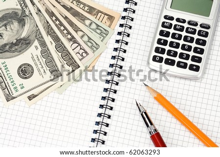pens, pensil, calculator and dollars on pad