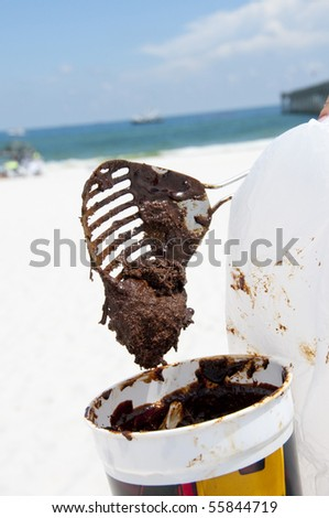 PENSACOLA BEACH - 23 JUNE:  A beachgoer collects sticky oil covered sand on June 23, 2010 in Pensacola Beach, FL.