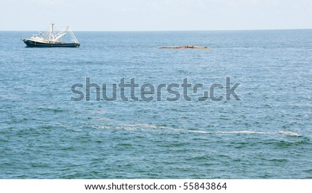 PENSACOLA BEACH - JUNE 23:  A boat skimming oil off the shore area is shown on June 23, 2010 near Pensacola Beach, FL