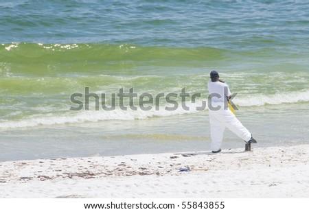 PENSACOLA BEACH - JUNE 23: A BP oil worker stands near the shore on June 23, 2010 in Pensacola Beach, FL.