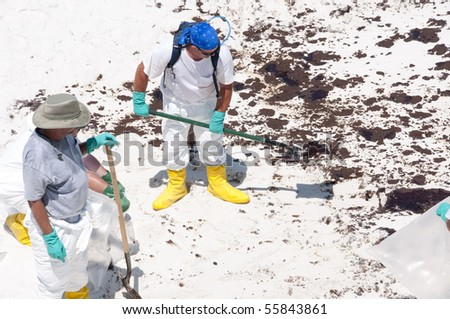 PENSACOLA BEACH - JUNE 23: A BP oil workers attempt to clean oil covered sand on June 23, 2010 in Pensacola Beach, FL. - stock photo