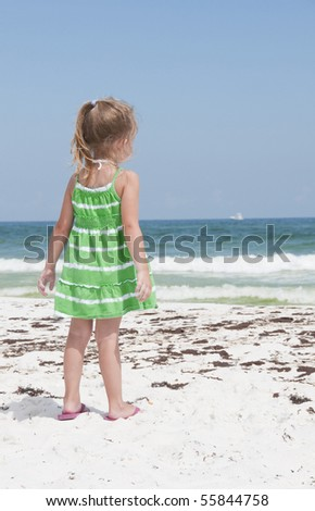 PENSACOLA BEACH - 23 JUNE: An unidentified young girl stands near oil covered sand on June 23, 2010 in Pensacola Beach, FL.