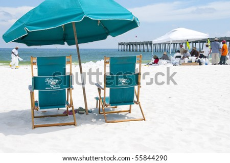 PENSACOLA BEACH - JUNE 23:  Beach chairs lie empty on June 23, 2010 in Pensacola, FL. BP oil workers work in the background.