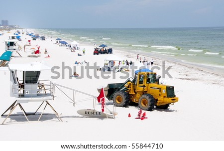 PENSACOLA BEACH - JUNE 23:  BP oil workers and heavy machinery work to clean oil covered sand on June 23, 2010 in Pensacola Beach, FL.