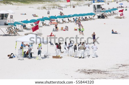 PENSACOLA BEACH - JUNE 23:  BP oil workers work among tourists on June 23, 2010 in Pensacola Beach, FL