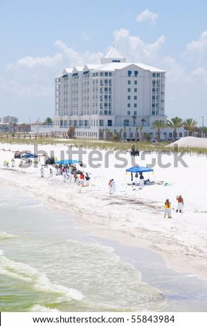 PENSACOLA BEACH - JUNE 23:  BP oil workers work as oil washes ashore on Pensacola Beach, FL on June 23, 2010. Jimmy Buffet\'s new Margaritaville Hotel opening soon in background.