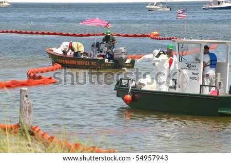 PENSACOLA - JUNE 10:  Oil spill workers in hazardous material suits collect oil-soaked debris on June 10, 2010 from the shores of Naval Air Station, Pensacola, FL.