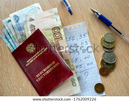 Pension certificate and Russian money on the table. Under them is a piece of paper with a budget estimate. Nearby coins and pen.