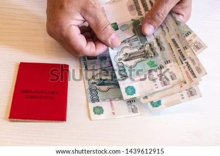 pension certificate, banknotes of 1000 rubles, the hands of a pensioner. The inscription on the certificate: 'pension certificate' #1439612915