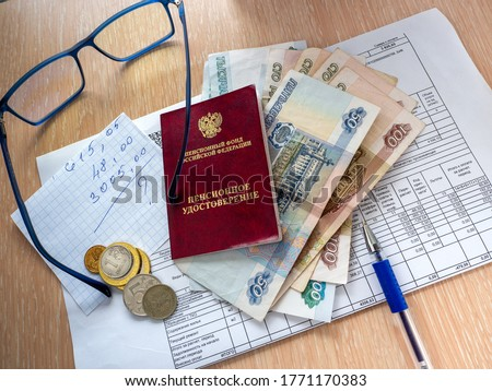 Pension certificate of the Russian Federation, Russian money and a sheet of paper are on the receipt for utilities. On the table is a pen and glasses.