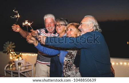 Pensioner friends having fun with fireworks sparklers - Senior people laughing and celebrating together outdoor after sunset - Focus on right man hand - Joyful elderly lifestyle and vacation concept