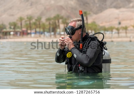 de9139cd0c87 Pensioner is underwater diver with breathing apparatus before deep driving  in sea. Recreational breath-