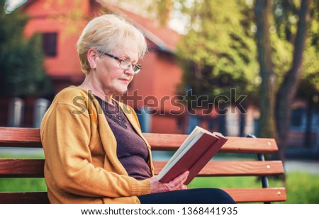 4dabbf2eae607 Retirement Concept. Pensioner time. Senior woman sitting in the park and  reading a book. Hobbies and