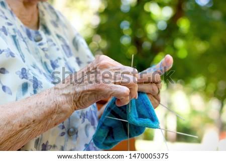 Pensioner woman knitting socks for her grandchildren, retiree lifestyle concept, enjoys in retirement Сток-фото ©