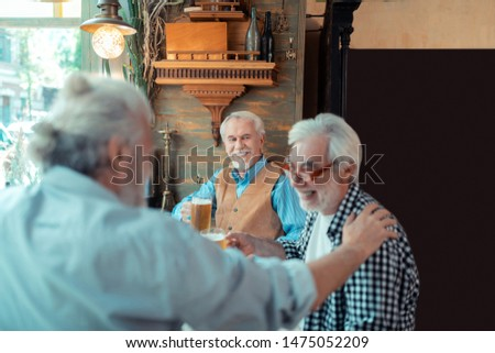 Pensioners laughing. Pensioners laughing while drinking beer in pub and talking #1475052209