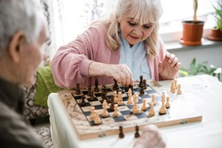 Pensioners pastime at senior home. Aged couple playing chess. Activities for seniors, elderly active lifestyle, older people time spending concept