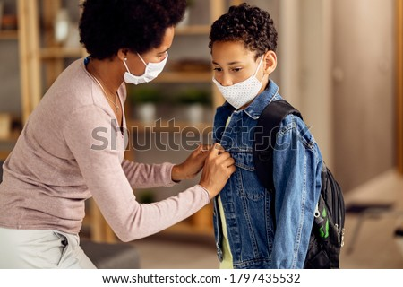 Pensive African American boy and his mother wearing protective face masks while getting ready to go back to school during coronavirus epidemic.