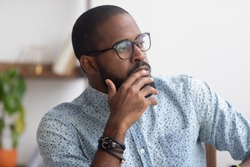 Pensive African American businessman pondering business strategy, serious employee thinking about project, problem solution, looking in distance, puzzled manager making decision, close up