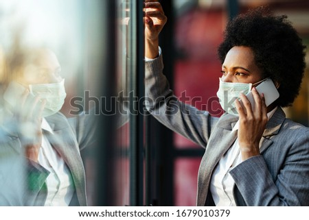 Pensive African American businesswoman communicating on mobile phone while wearing protective face mask and looking through the window.