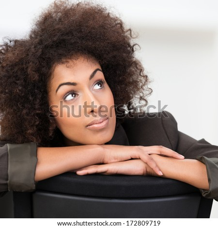 Pensive African American businesswoman with curly afro hair sitting with her arms on the back of the chair staring up into the air in contemplation