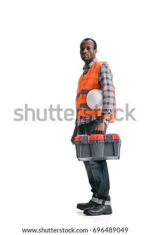 pensive african-american construction worker with toolbox isolated on white
