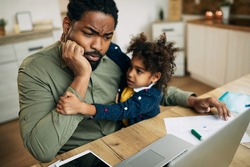 Pensive African American father working on laptop while daughter is seeking his attention at home.