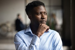 Pensive African American male employee look in distance thinking planning or visualizing, thoughtful biracial businessman lost in thoughts pondering over problem solution, business vision concept