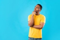 Pensive African American Man Thinking Touching Chin Looking Aside Posing Standing On Blue Background. Studio Shot Of Thoughtful Black Millennial Guy. Let Me Think Concept