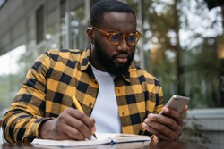 Pensive African American man using mobile phone, taking notes, working freelance project online, sitting outdoors. Serious student studying, learning something
