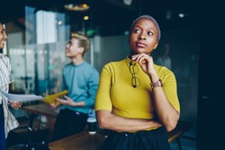 Pensive African American woman holding optical glasses in hand and thoughtful thinking on information, contemplative female with dark skin standing in coworking space and pondering looking away