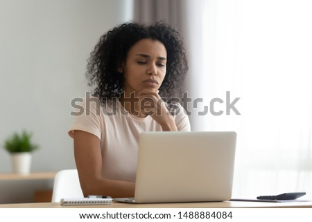 Pensive african American young woman sit at desk thinking studying or working on laptop at home, thoughtful black millennial girl student pondering considering idea looking at computer screen