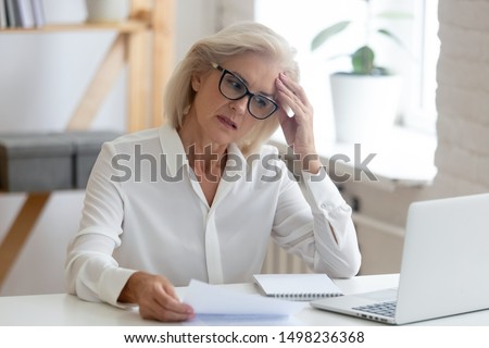 Pensive aged businesswoman in glasses sit at office desk thinking of problem solution, thoughtful senior woman worker in glasses look at laptop screen hold document pondering or making decision