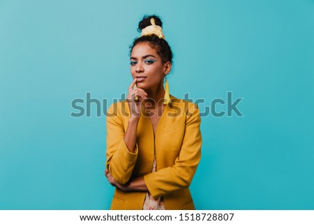 Photo of  Pensive amazing african girl looking to camera. Indoor portrait of curious lovely woman wears elegant yellow jacket.