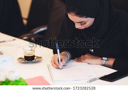 Pensive Arab woman planning working schedule writing in notebook while sitting at working place, Arabic female administrative manager making notes of information browsed on netbook. Foto d'archivio ©
