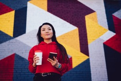 Pensive Asian youngster with takeaway cup and mobile phone thinking at urban setting with street art, trendy dressed generation Z holding cellular gadget and coffee to go spending leisure in city