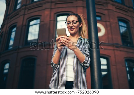 Pensive attractive woman in cool eyeglasses checking notification on smartphone connected to 4G while reading news in website.Cute pondering female sending messages to friends during spring walk #752026090