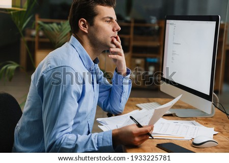 Pensive attractive young entrepreneur looking through paperwork while sitting at the desk