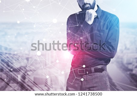 Pensive bearded businessman standing over skyscraper background with double exposure of network hologram. Toned image