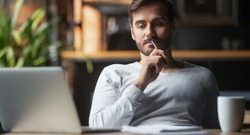Pensive bearded man sitting at table drink coffee work at laptop thinking of problem solution, thoughtful male employee pondering considering idea looking at computer screen making decision