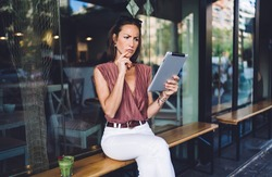 Pensive beautiful woman in trendy wear resting near cafe holding digital tablet confused with messages, female influencer using touchpad for browsing and share publication and media content online