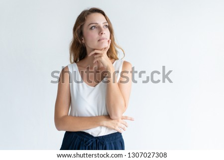 Pensive beautiful woman touching chin with fingers. Young lady standing and looking away. Contemplation concept. Isolated front view on white background.