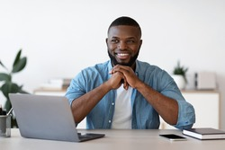 Pensive Black Man Office Worker Sitting At Desk With Laptop And Smiling. Handsome African American Freelancer Guy Thinking About Business Strategy At Workplace, Resting Chin On Hands And Looking Away
