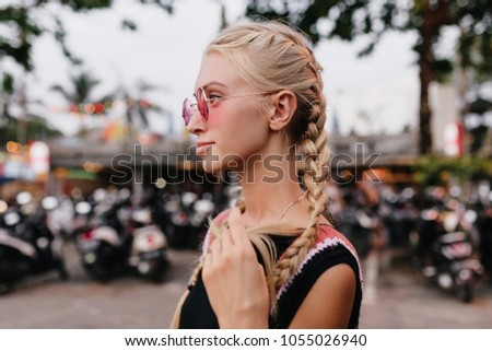 Pensive blonde woman in black attire posing on blur street background. Outdoor shot of serious tanned lady with braids wears pink sunglasses.