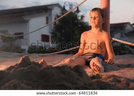 pensive boy after a bath sits in the sand on the beach at evening