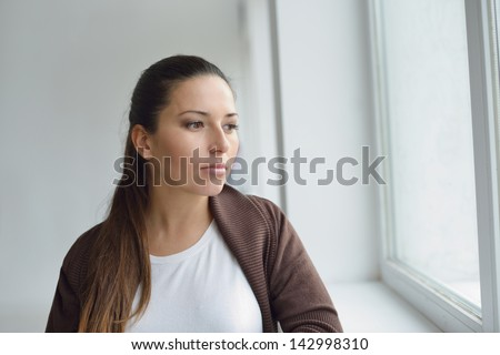 pensive brunette woman near the window
