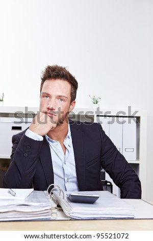 Pensive business man with files sitting at desk in office